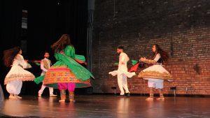 Brightly dressed dancers performing on stage