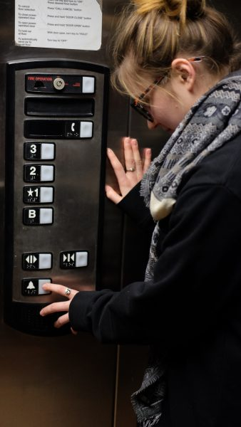 Person in an elevator pressing the alarm button