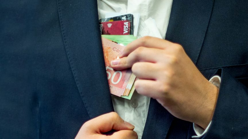A man in a suit pockets credit cards and money.