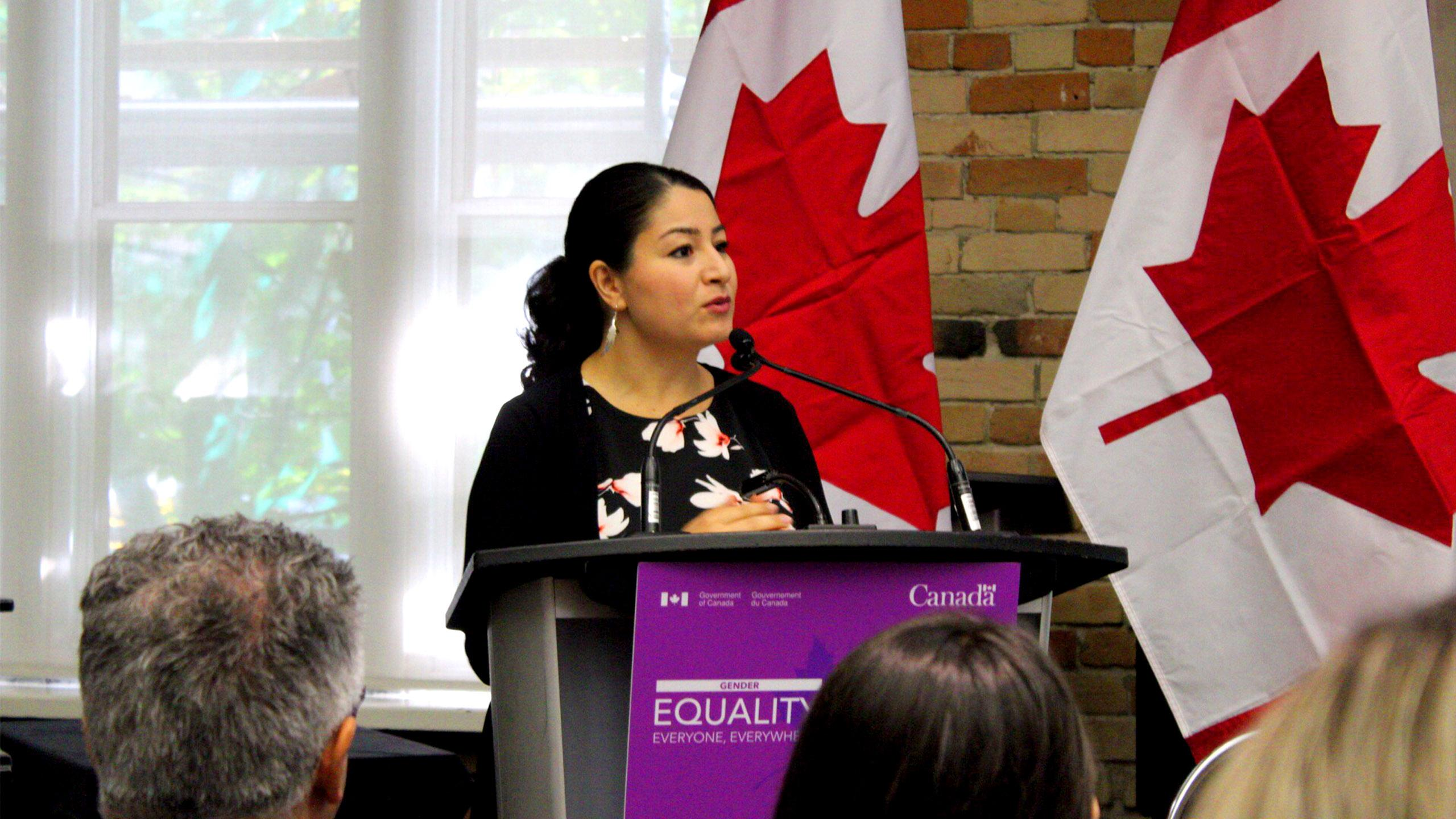 Minister for Women and Gender Equality Maryam Monsef speaks at a podium in front of Canadian flags
