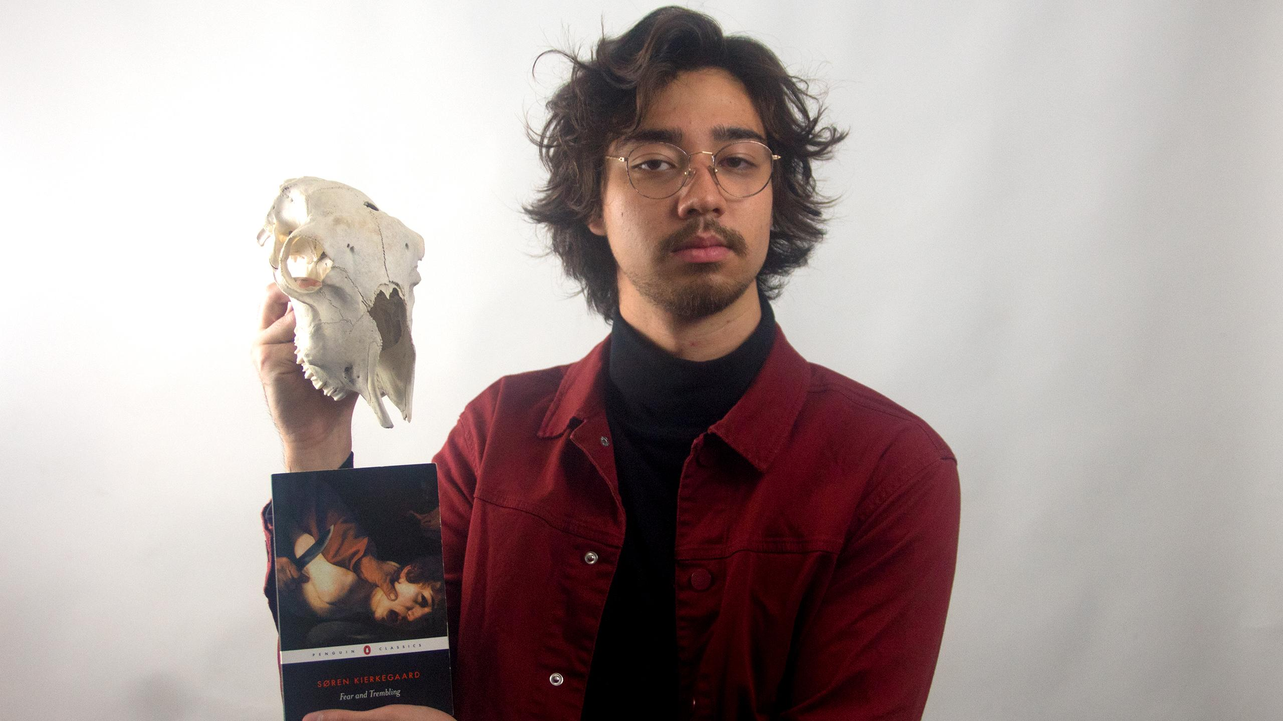 "Artsy looking man wearing glasses holding a skull of an animal on one hand and the book ""Fear and Trembling"" on the other hand"