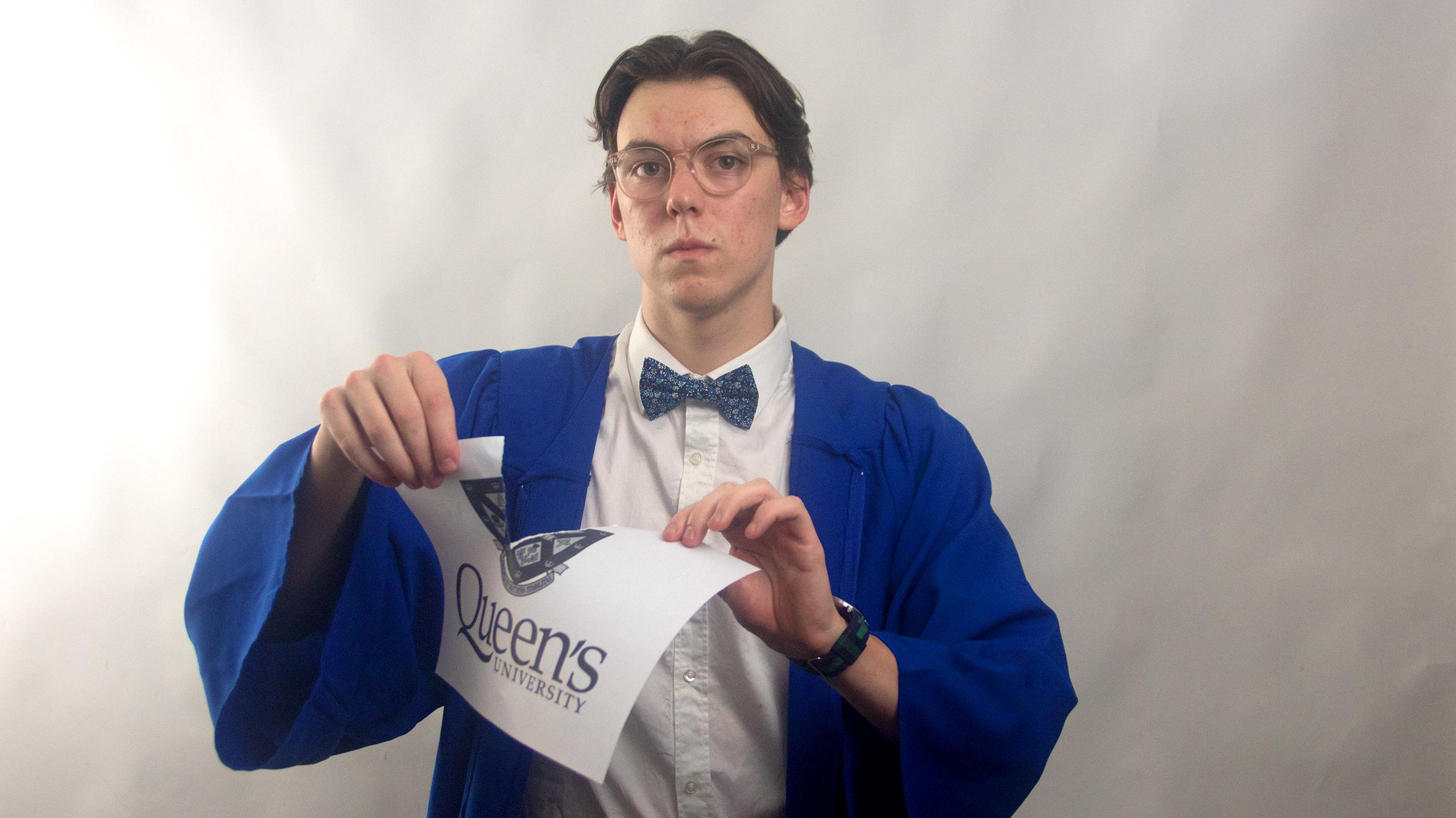 A serious looking guy with glasses wearing a button up shirt and bow tie ripping a paper with the Queen's logo