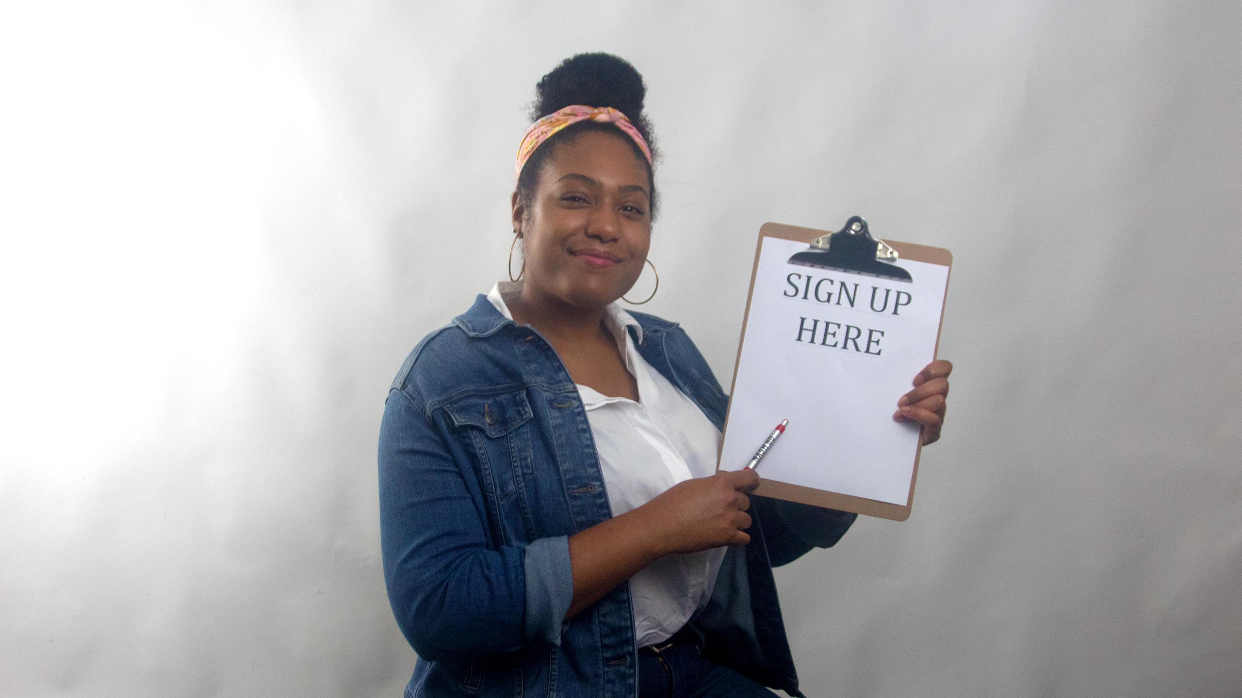 "A happy approachable girl wearing a white shirt and blue denim jacket holding a clipboard with the words ""Sign Up Here"" on the clipboard"
