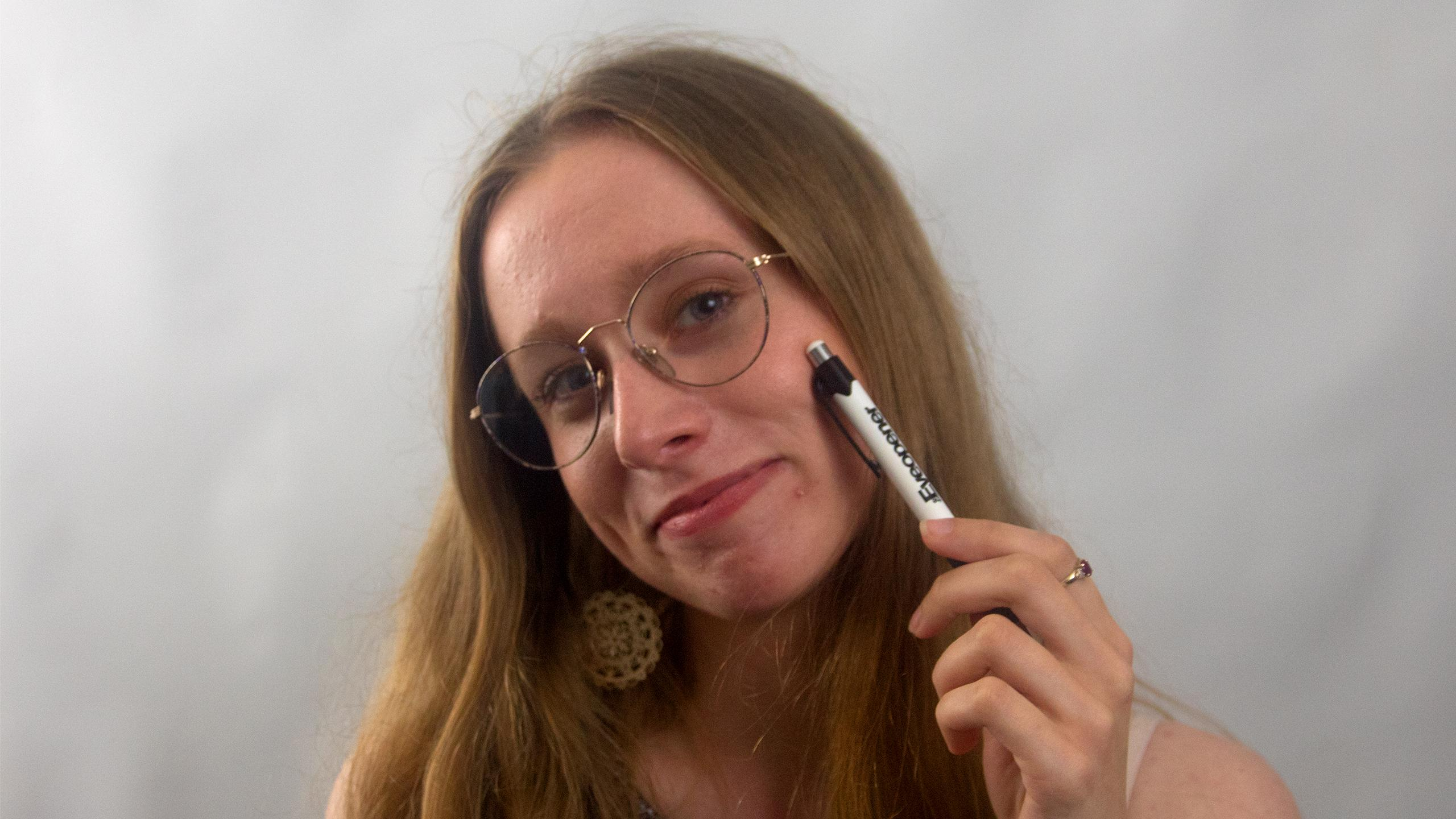 Smiling girl with glasses holding a pen to her cheek