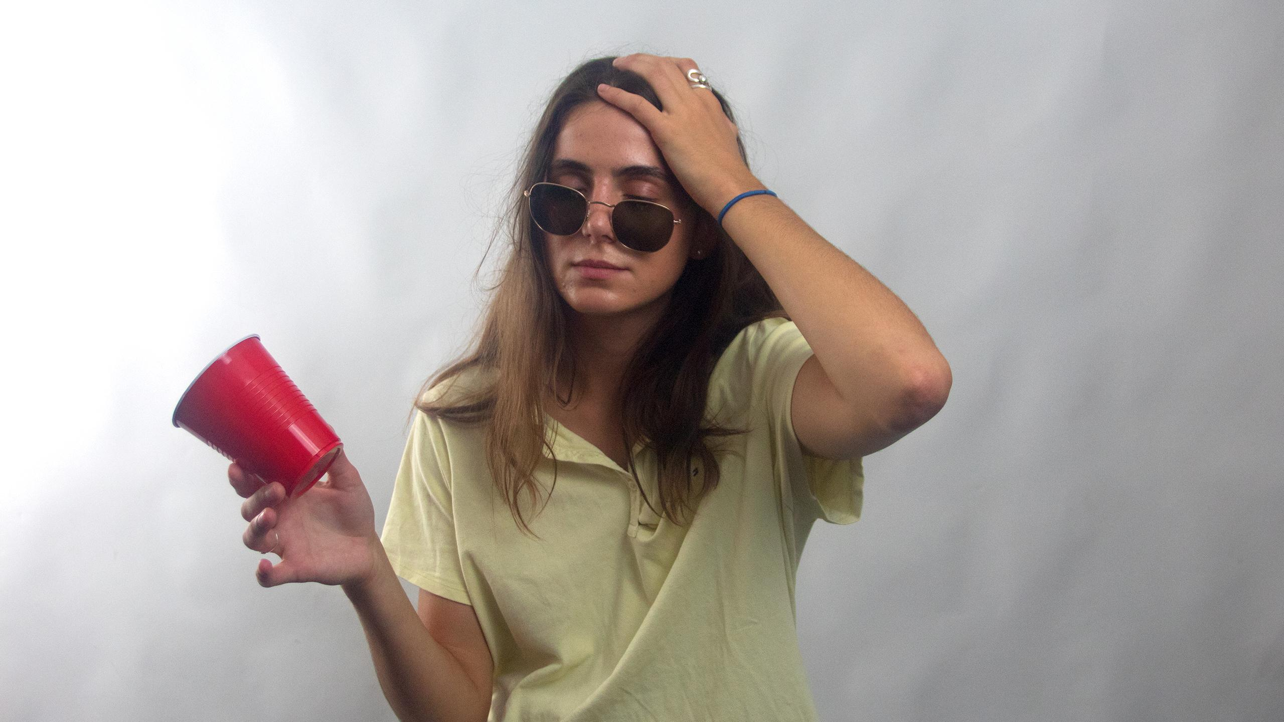 Hungover girl wearing askew sunglasses and a yellow polo shirt with mismatched buttons holding a red solo cup in one hand and the other hand holding her head