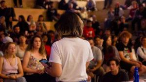 An individual stands in front of a crowd of listeners in the SLC, speaking to the strike
