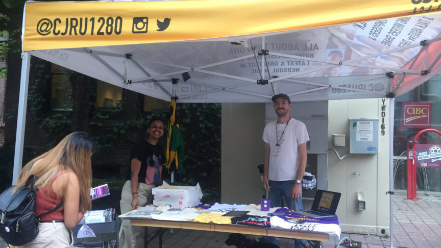 Two radio station workers stand behind a table of t-shirts and other free apparel underneath a yellow tent labelled CJRU.