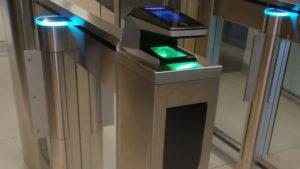 A photo of the biometric scanner in the HOEM building, a metal machine with a green and blue light scanner