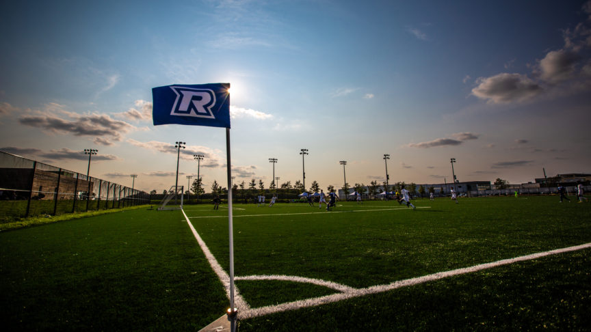 A photo of the Ryerson soccer field at sunset with a Ryerson flag in the middle