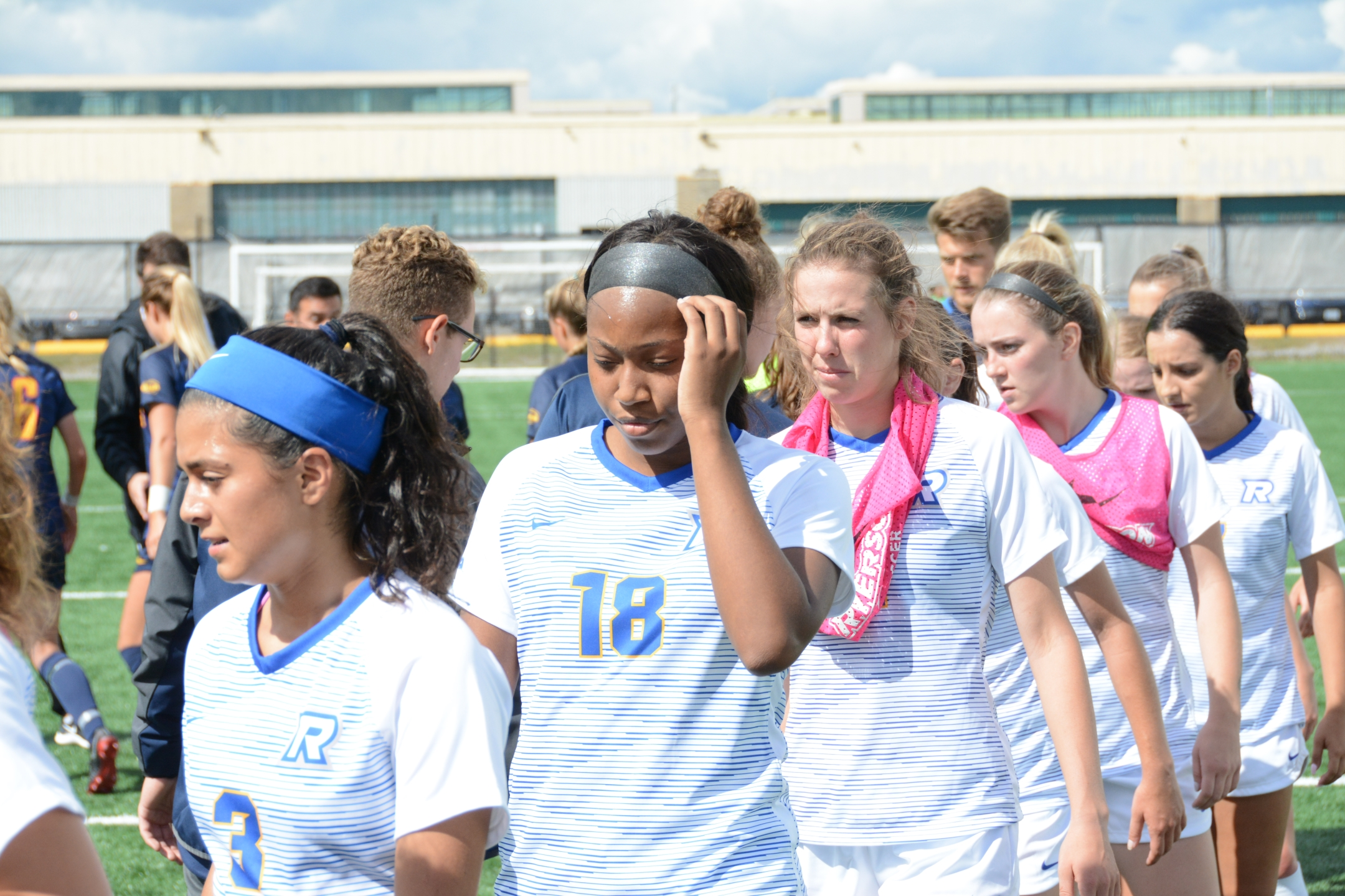 A photo of female Ryerson soccer players high-fiving another team and looking contrite