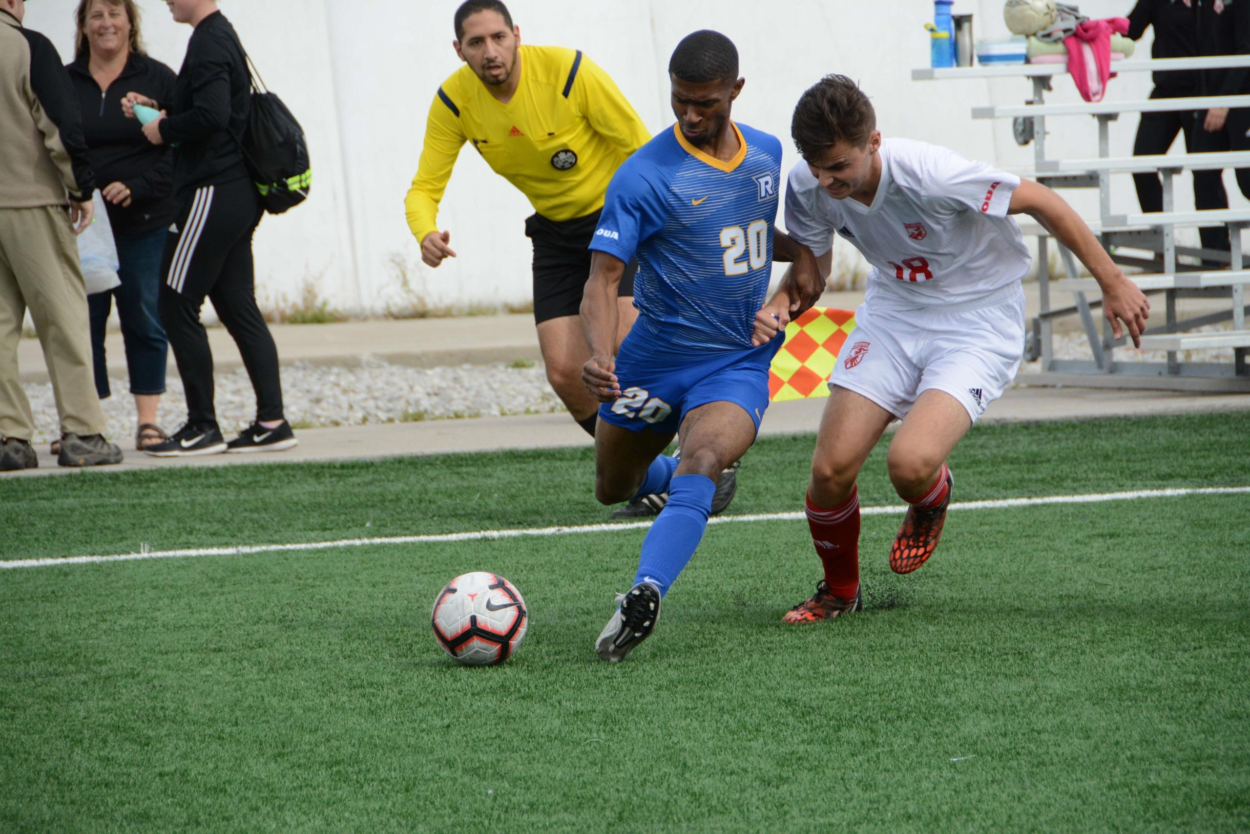 A photo of a male Ryerson student and a male student from another school going head to head in soccer game