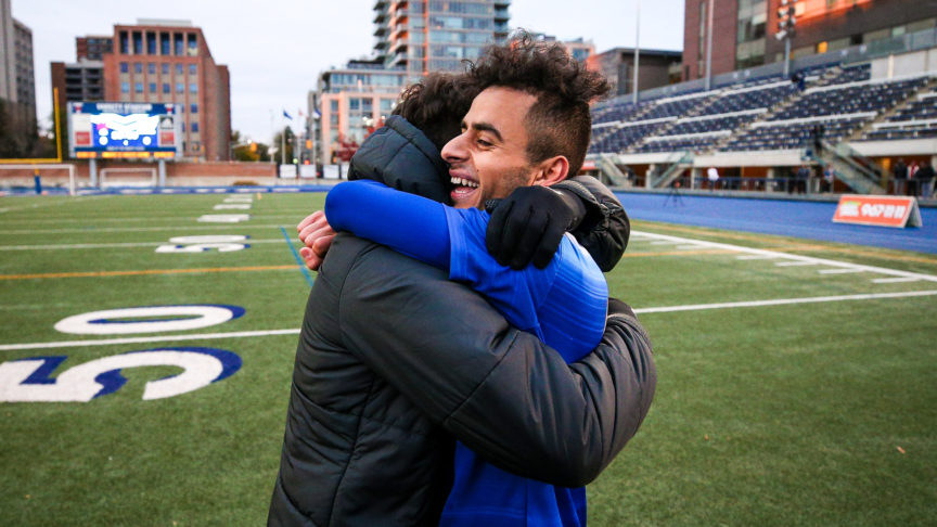 a man wearing a jacket is embraced by a soccer player wearing a blue jersey