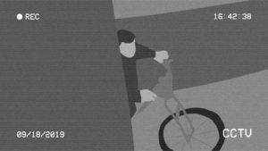 A black and white illustration of a man stealing a bicycle edited to look like a shot from CCTV footage