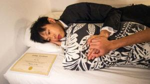 Student lies in bed solemnly with a degree next to him