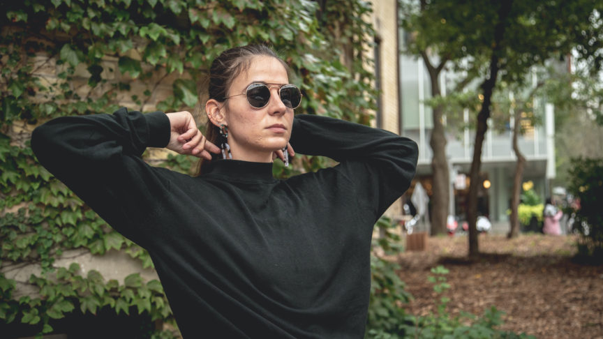 A photo of a student in a black turtleneck and sunglasses pulling on the collar of their sweater