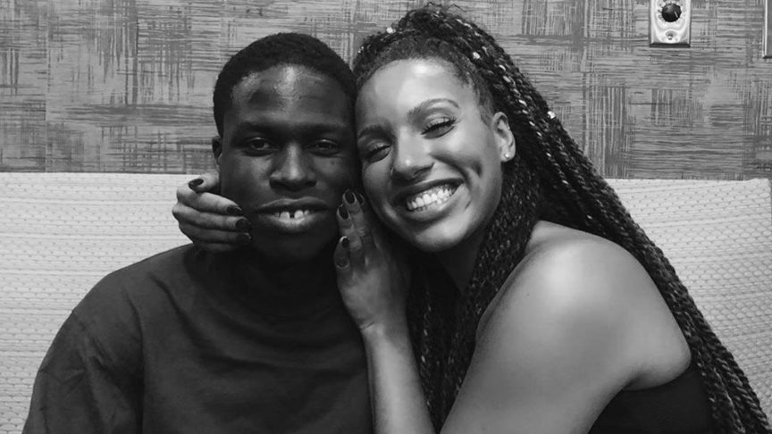 Elise Mariah Armstrong-Peart smiling with and embracing Daniel Caesar.