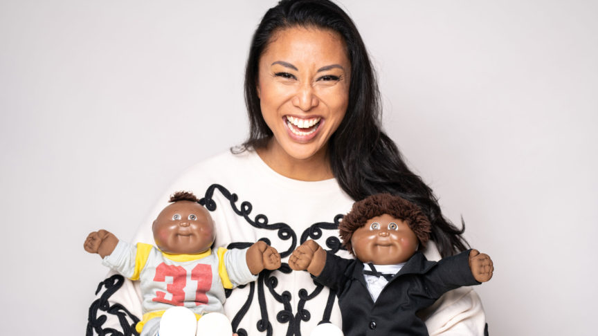 Author Catherine Hernandez holding two Black, male dolls.