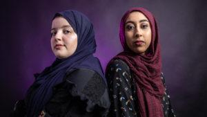 Two hijabi women, one of lighter and one darker complexion, stand side by side