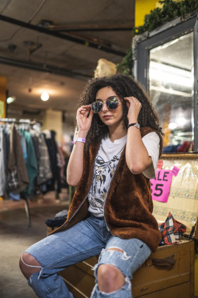 A person sits on a trunk of clothing in Black Market. They have sunglasses on their face and are wearing a fur vest, ripped jeans and t-shirt with a tiger's face on it.