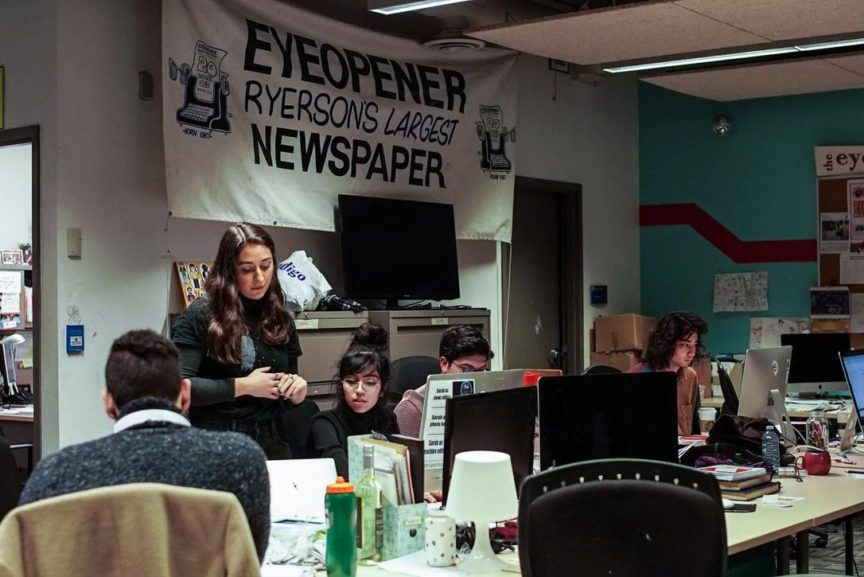 Photo of four Eye editors sitting at their desks, working on production in the office, SCC 207.