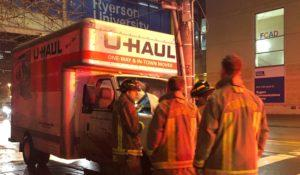Firefighters stand in front of the traffic light post where a U-Haul truck collided.