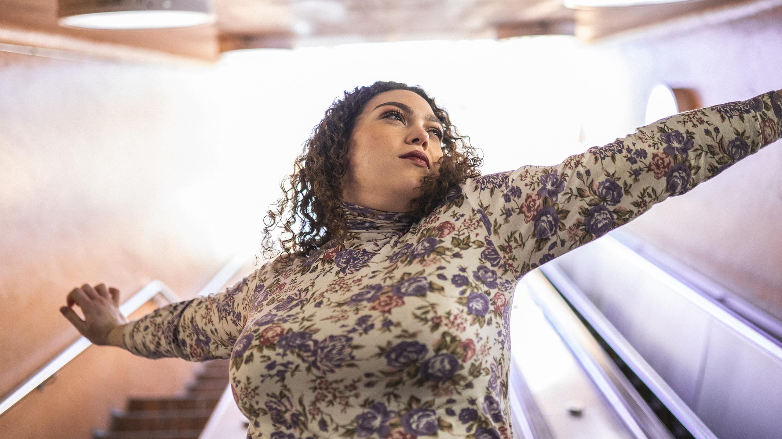 A picture of a plus-sized woman stretching out her arms and looking off camera