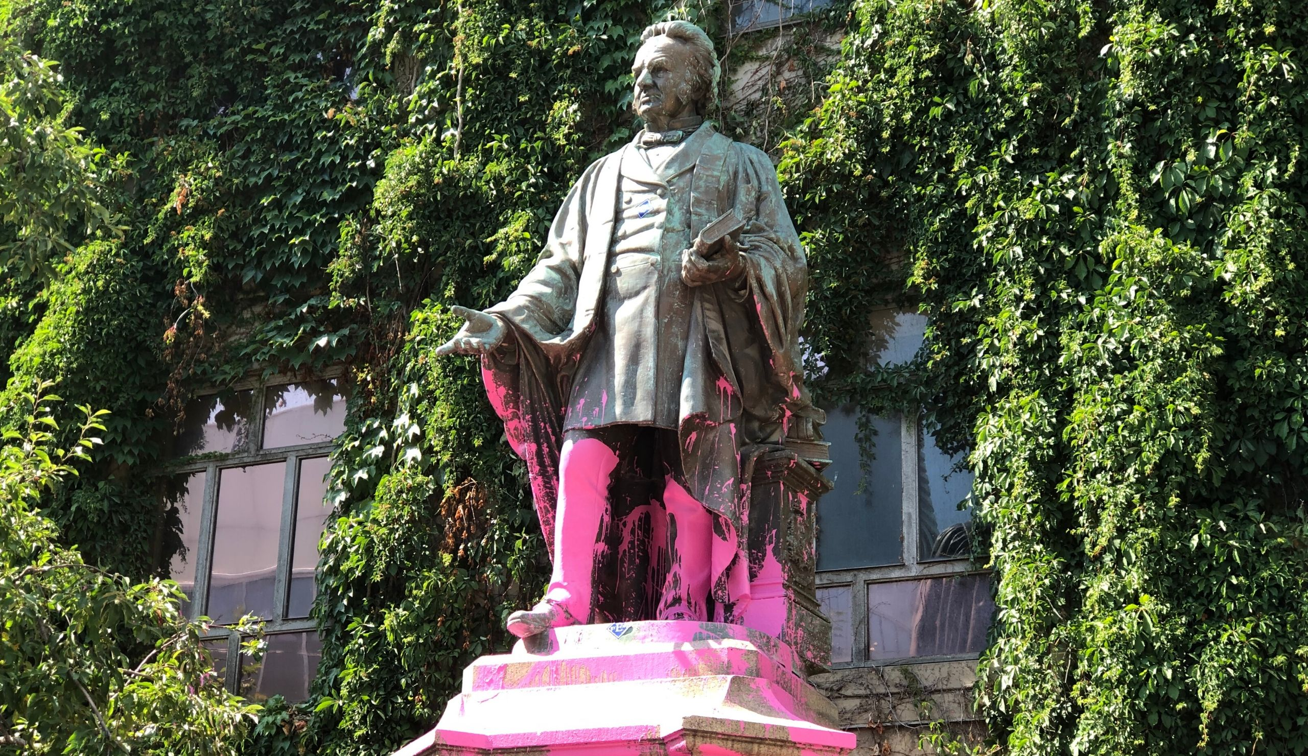 A tall statue of Egerton Ryerson stands against a green, mossy wall. The bottom of the statue has been splashed with pink paint.