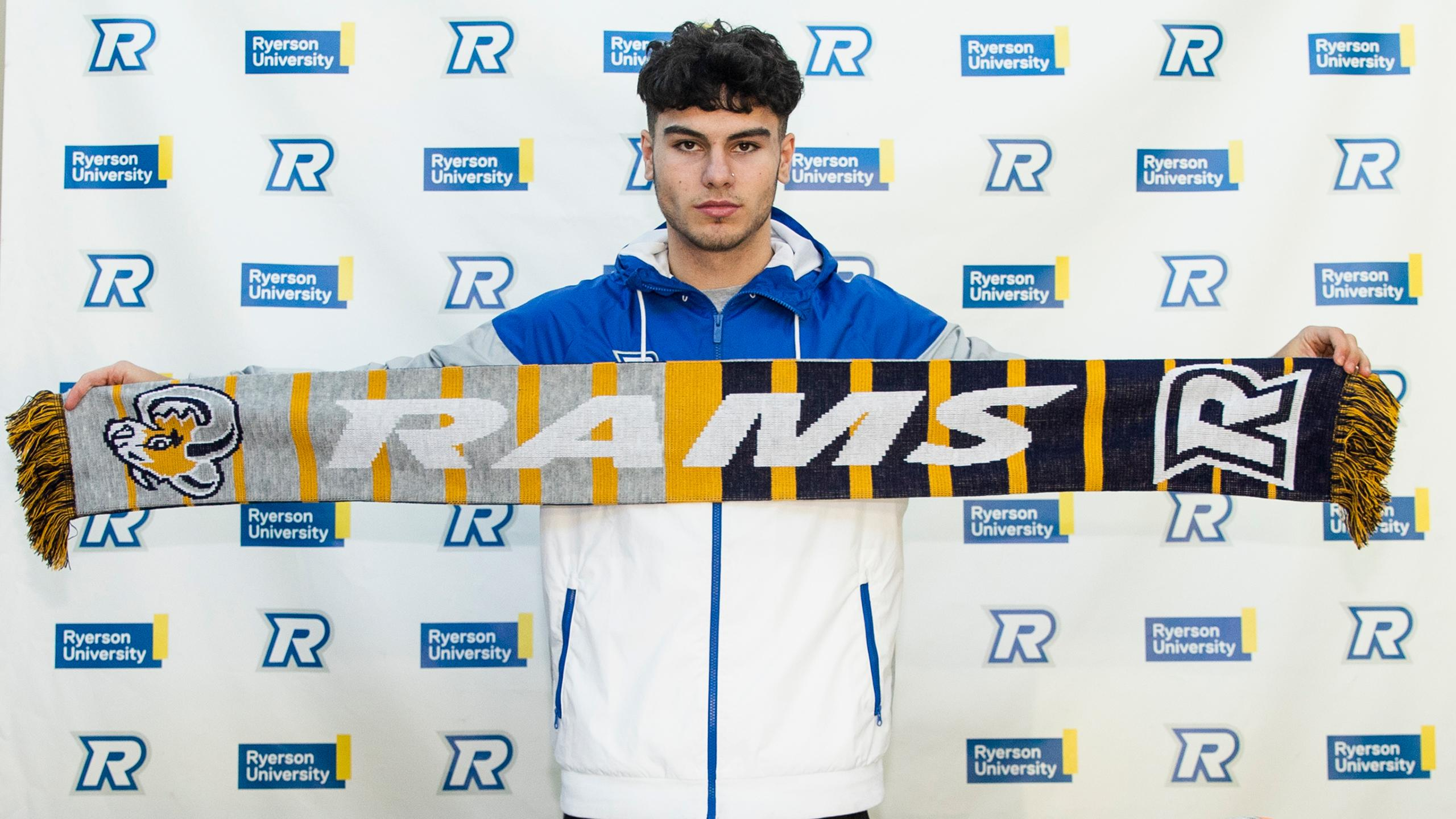 Photo of Abdallah El-Chanti displaying a scarf with the Ryerson Rams logo and wearing a Ryerson Rams jacket.