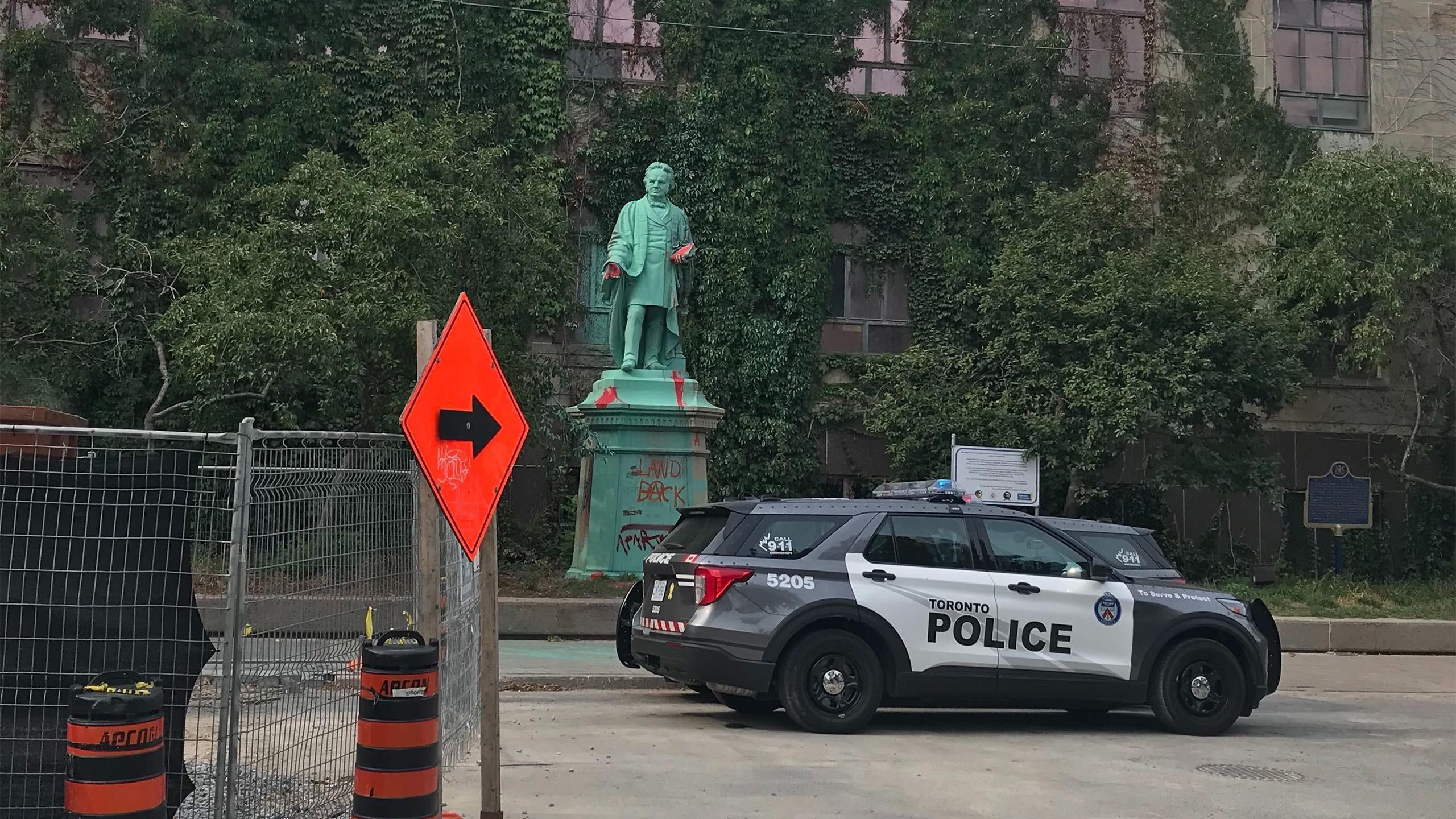 Photo of a Toronto Police car in front of the Egerton Ryerson statue on Gould Street.