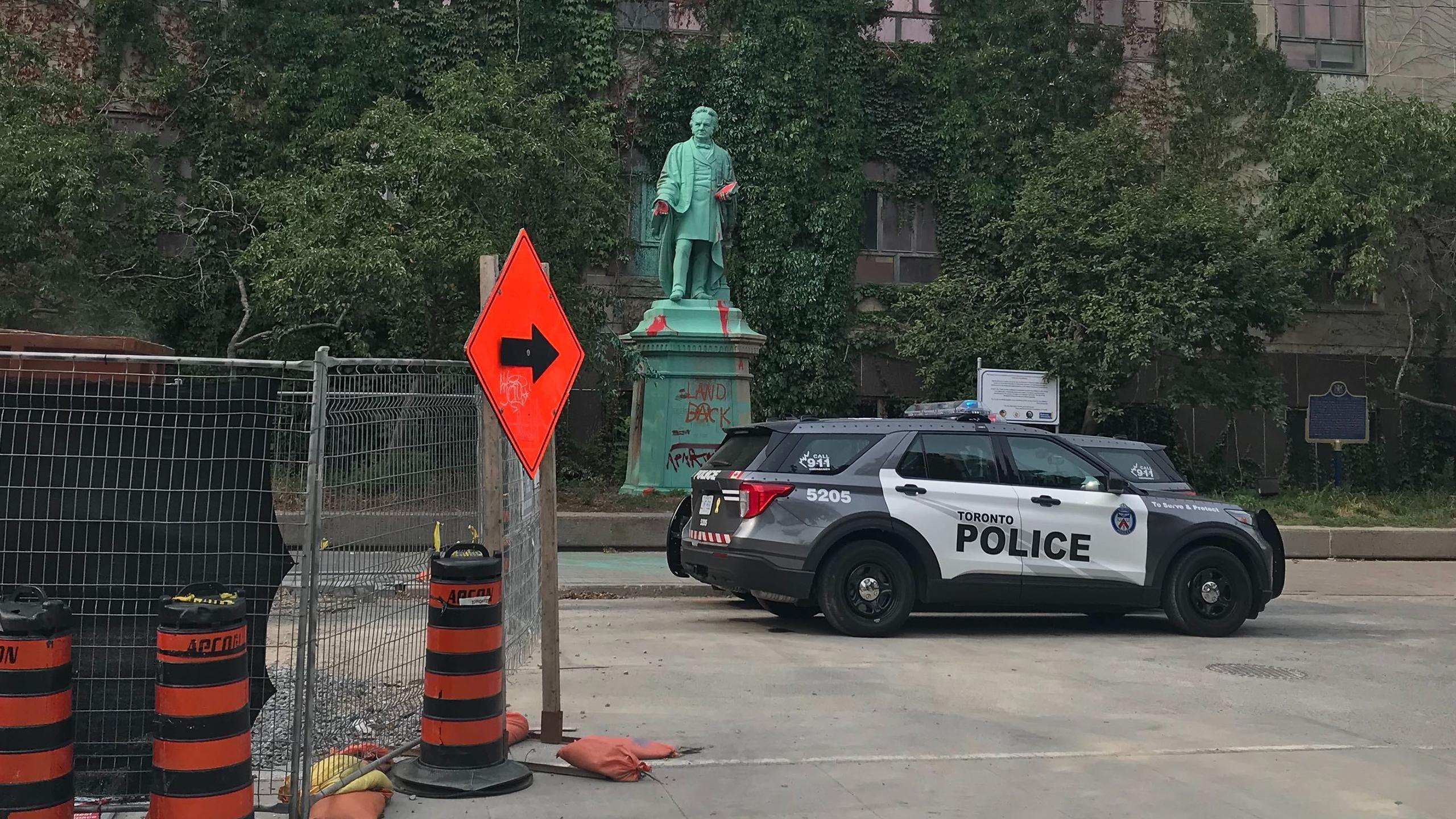 Photo of a Toronto Police car in front of the Egerton Ryerson statue of Gould Street.