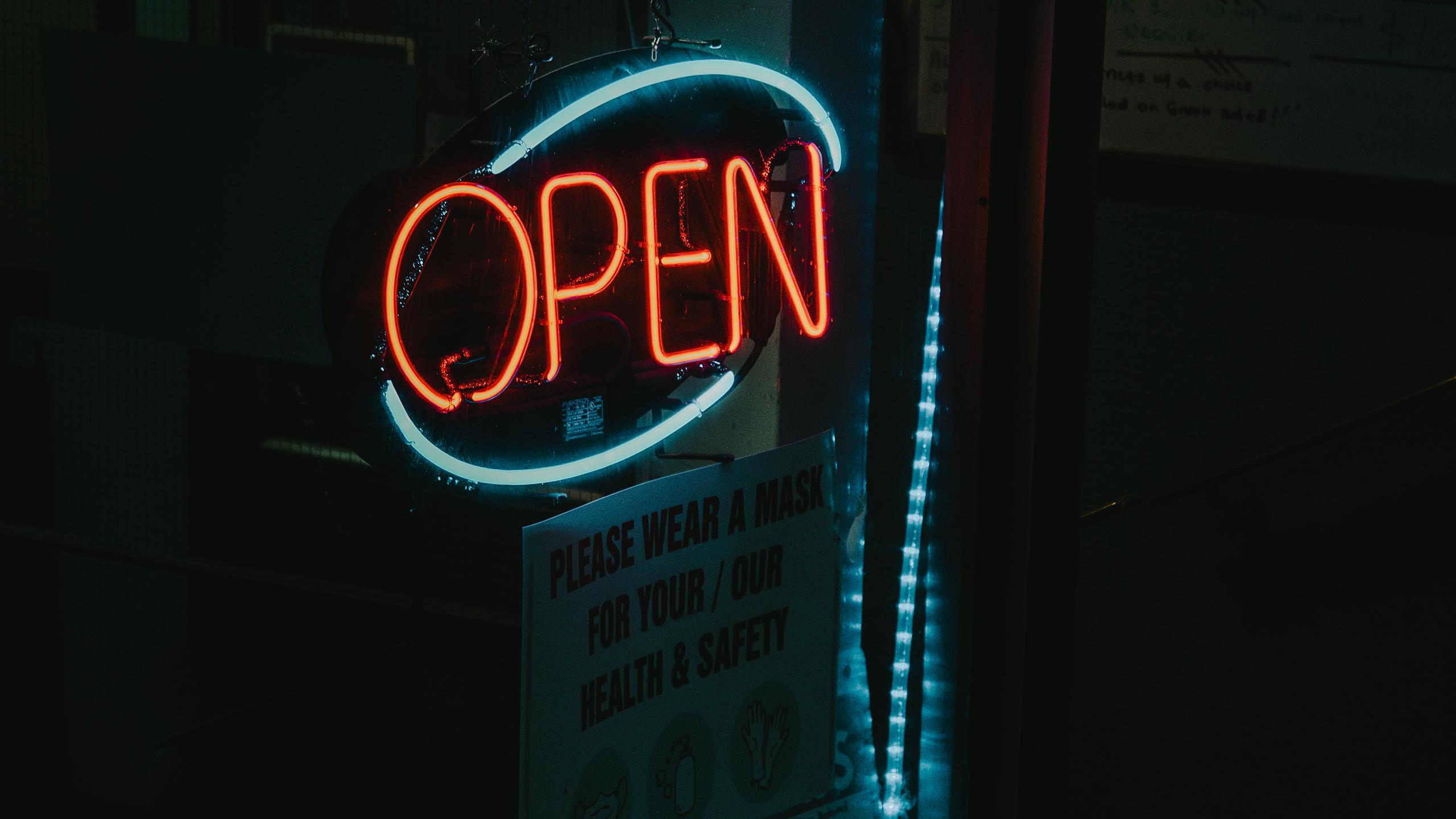 "A picture of a neon open sign. Underneath, a smaller white cardboard sign says ""please wear a mask for your/our health & safety."""