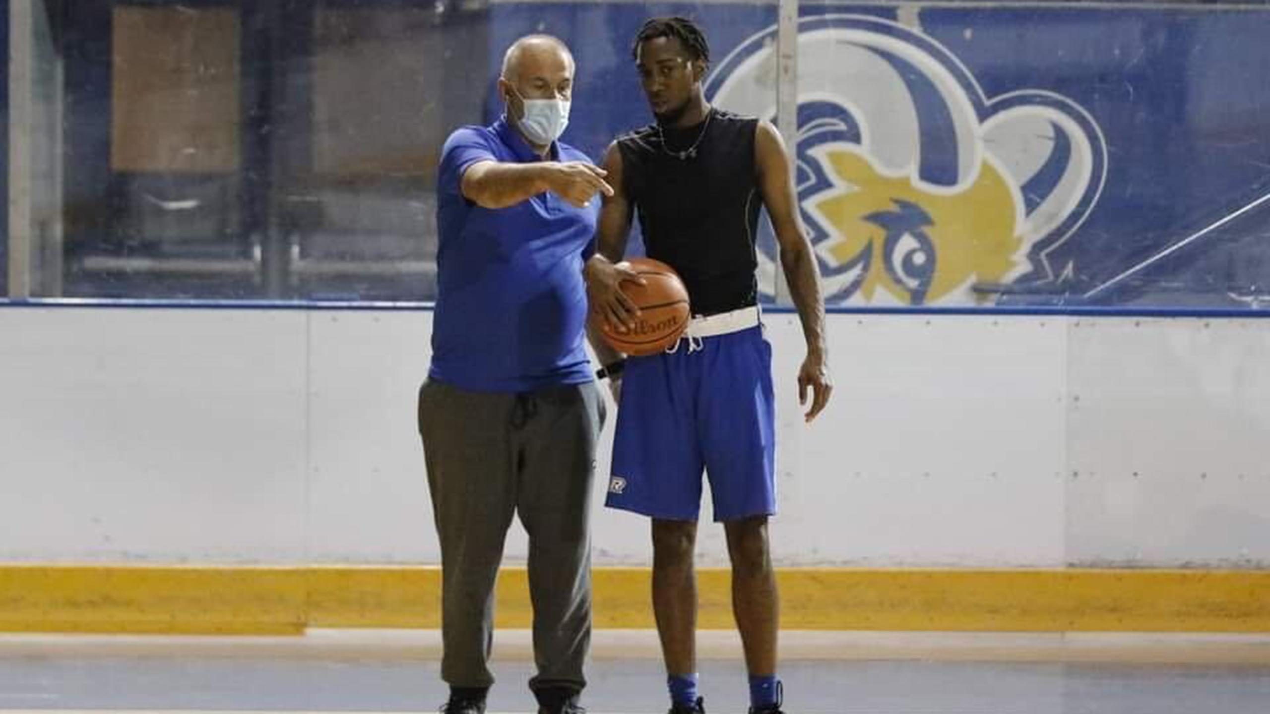 Photo of a coach and an athlete holding a basketball.