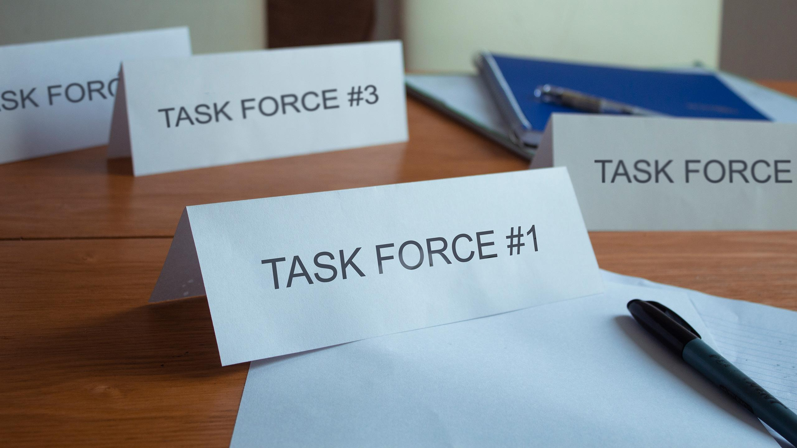 Photo of with 4 name cards that say Task Force #1, Task Force #2, etc. with pens and papers scattered on a desk.