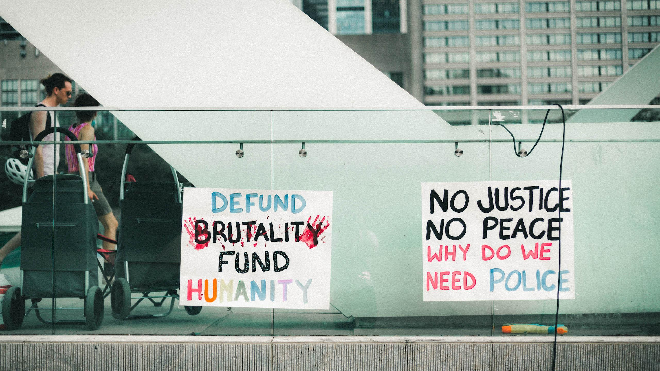 One sign reads: defund brutality, fund humanity; another sign reads no justice, no peace, why do we need police