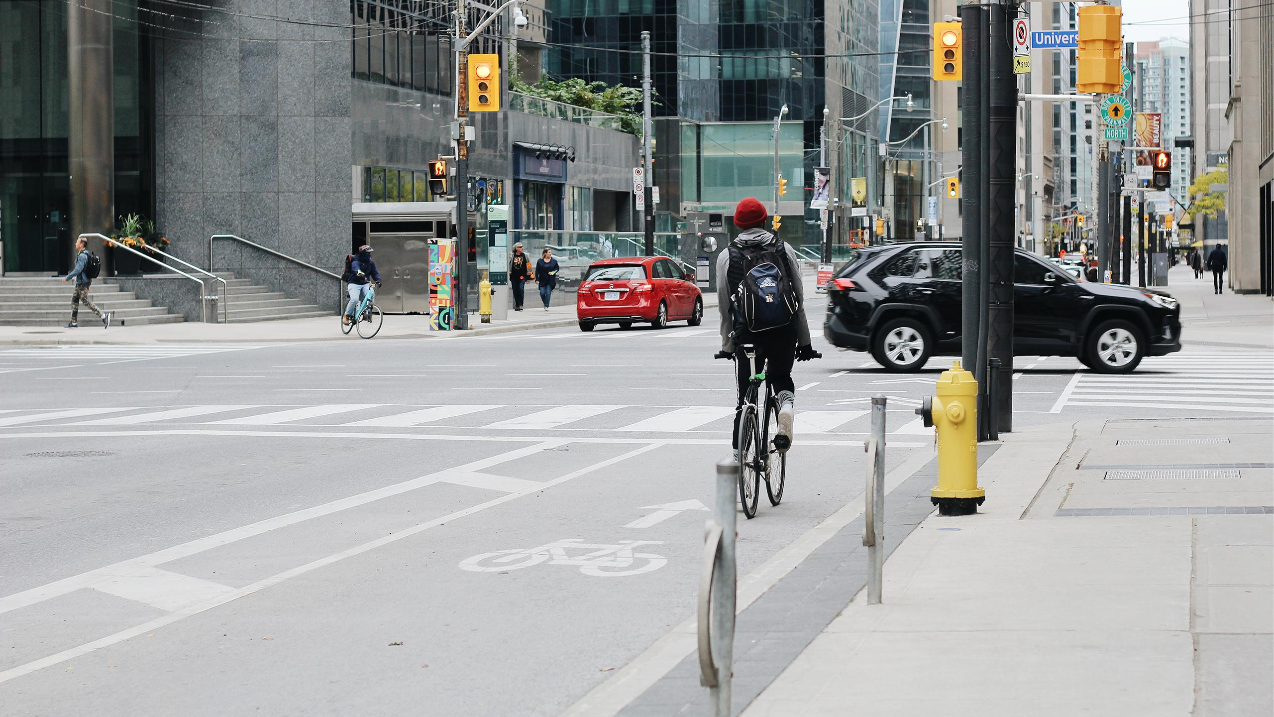 Person riding a bicycle in a bike lane in downtown Toronto.