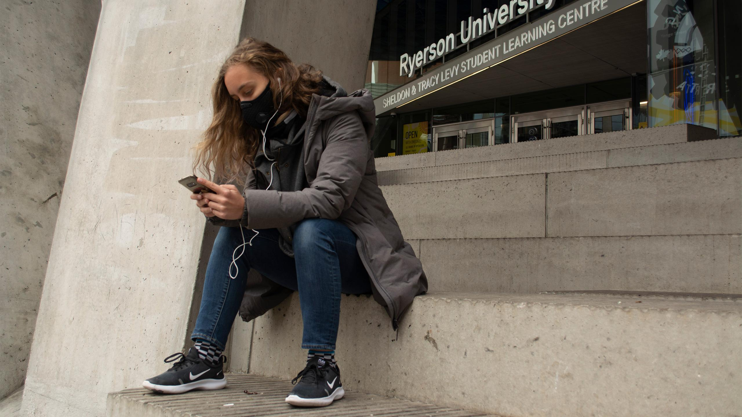 Student wearing a mask sitting on the steps of SLC looking at their phone.