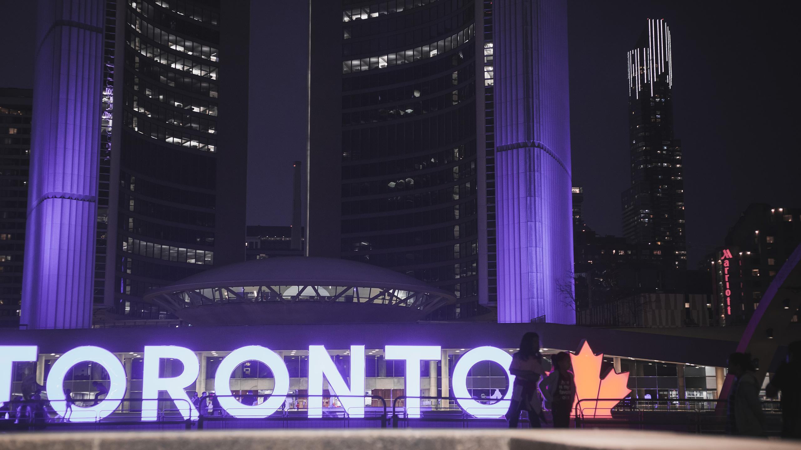 Toronto city hall behind the Toronto sign at night.