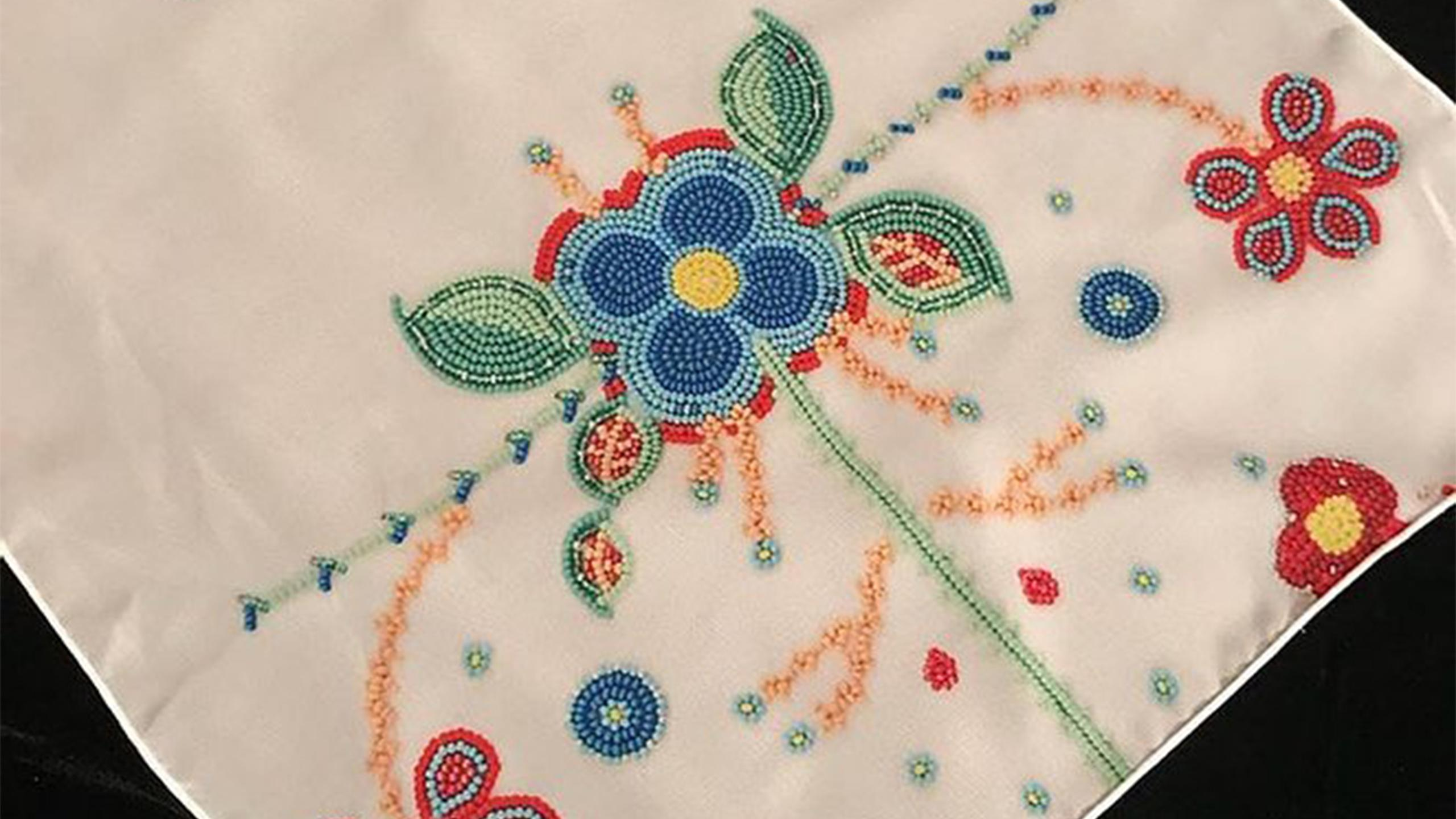 Beaded fabric with an intricate floral pattern.
