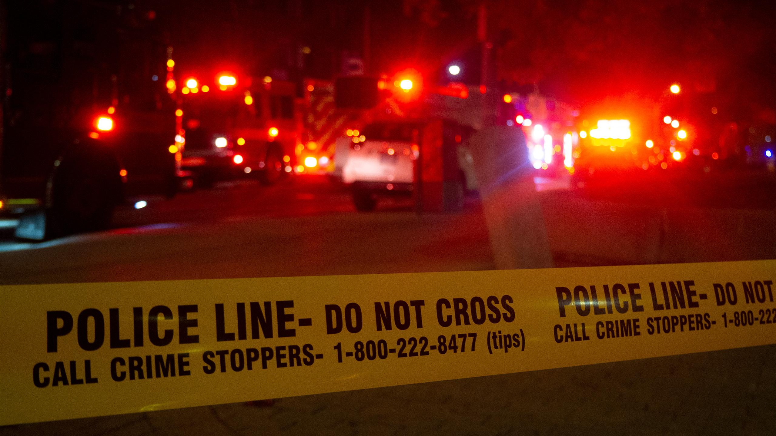 Police tape in front of a street with several firetrucks and emergency response vehicles.