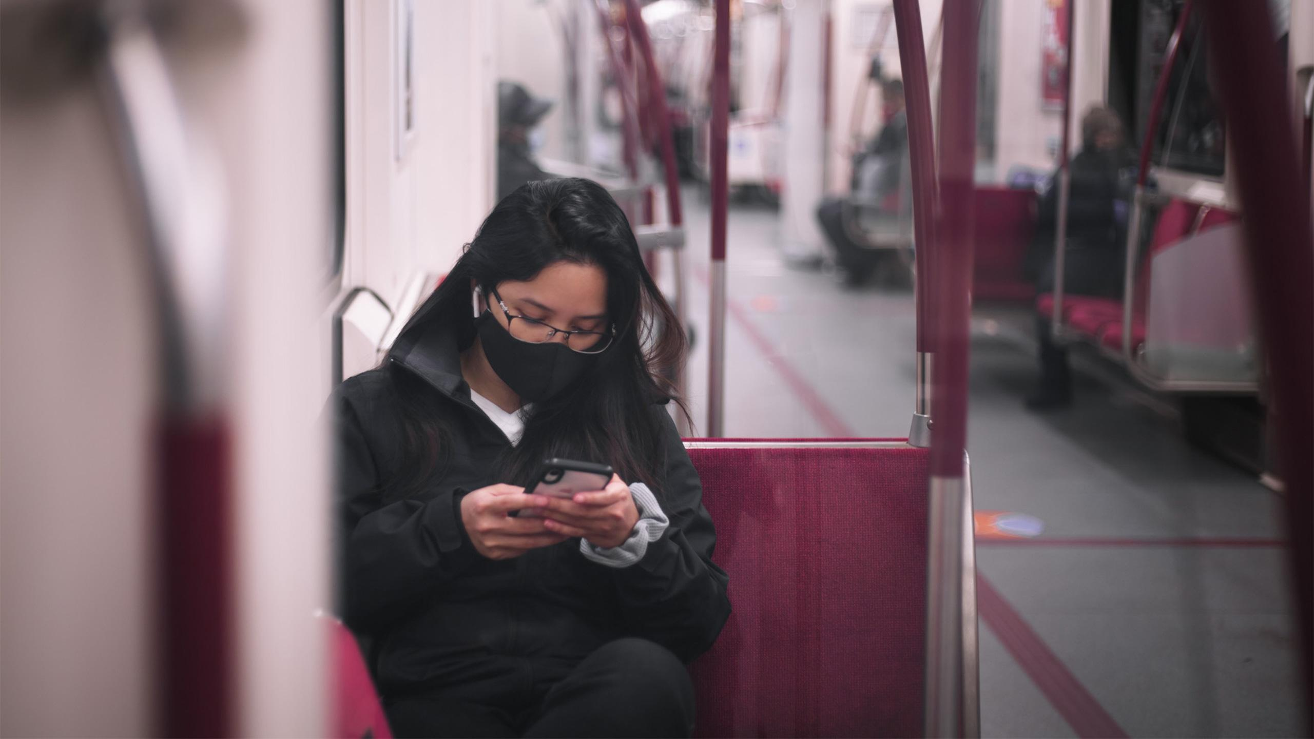 Woman wearing a mask sitting on the TTC subway looking at her phone.