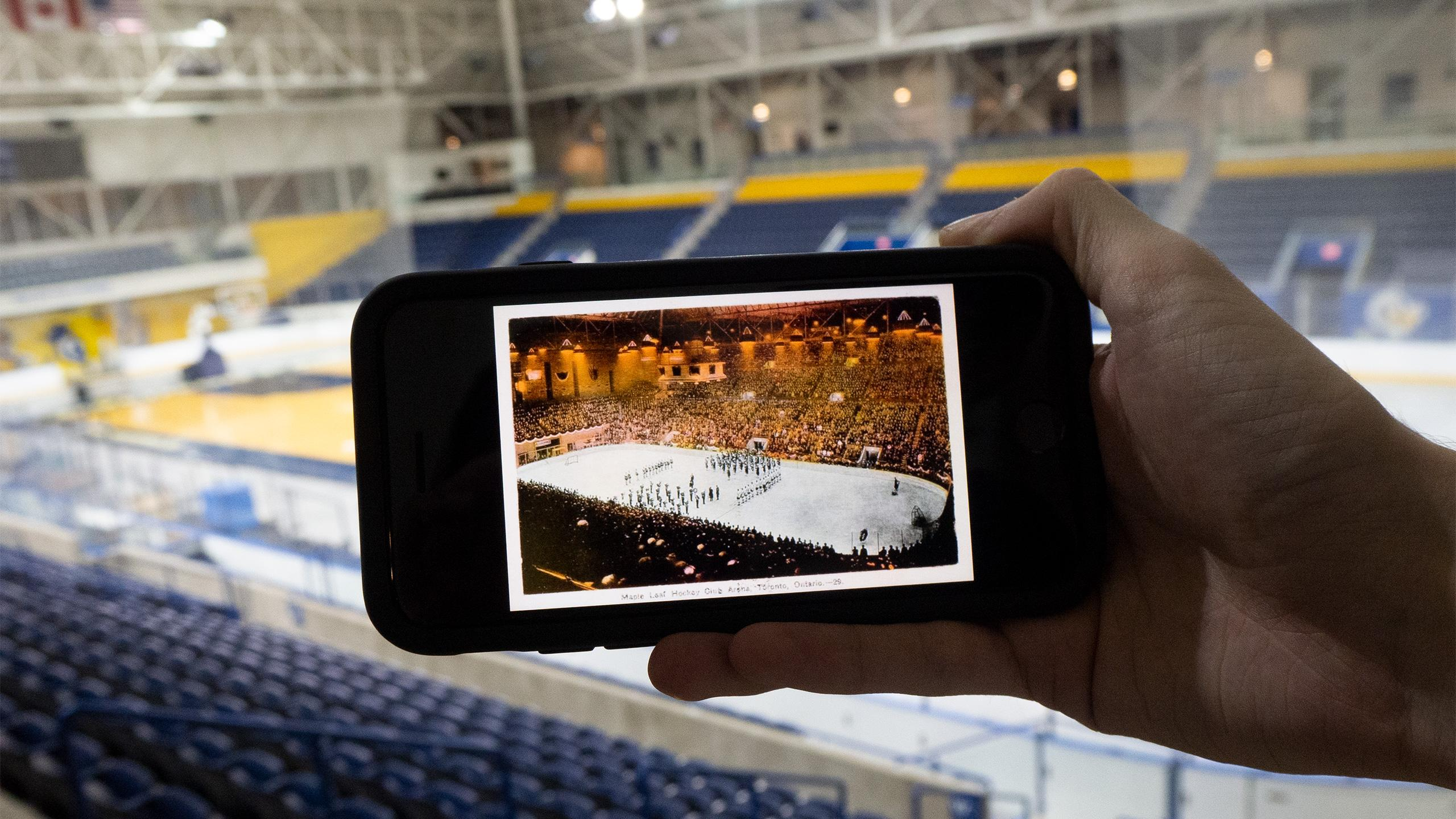 Someone holding up a picture of the old Maple Leaf Gardens arena in front of the current MAC arena.