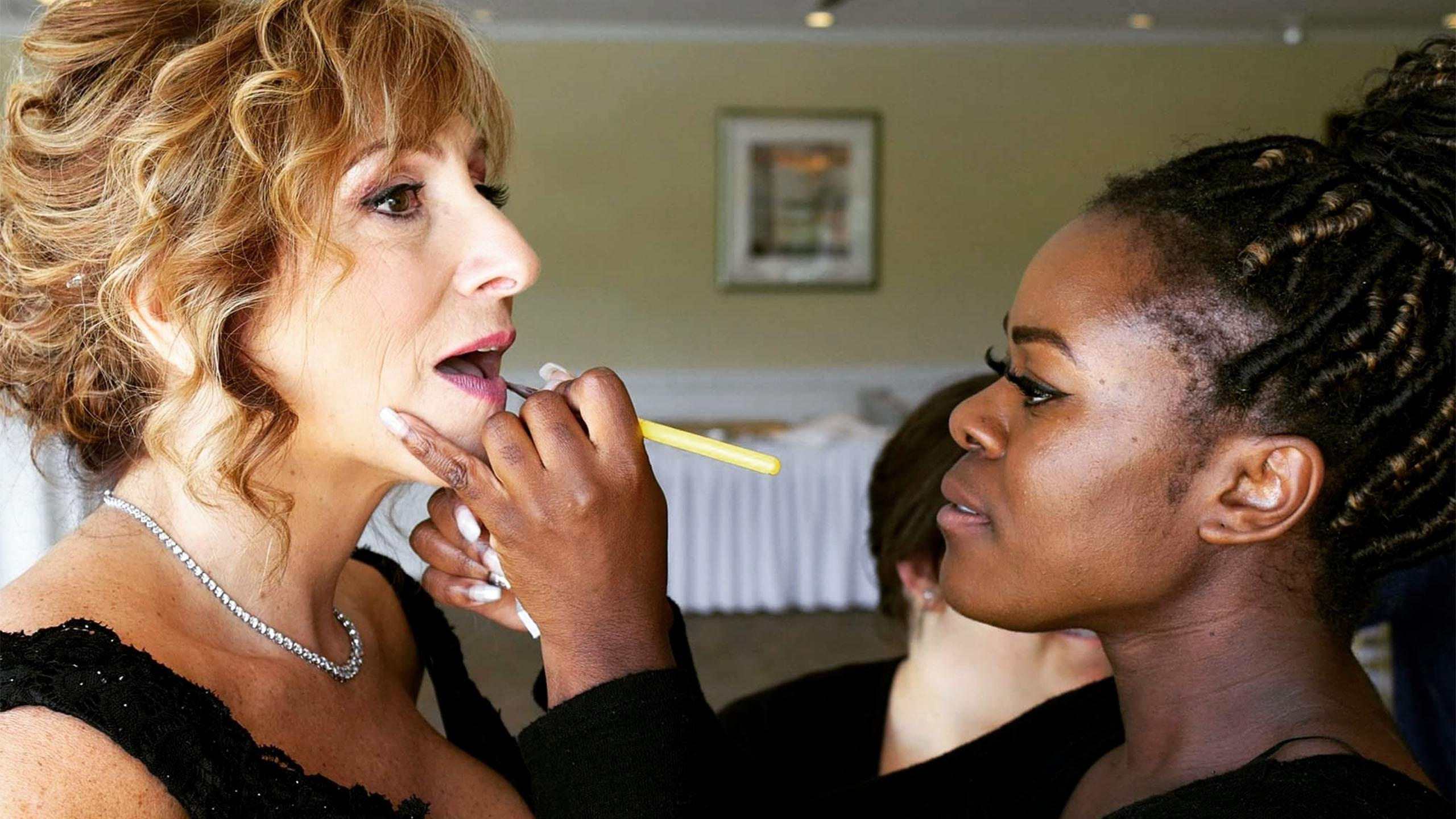 A woman applying lip makeup to another woman.