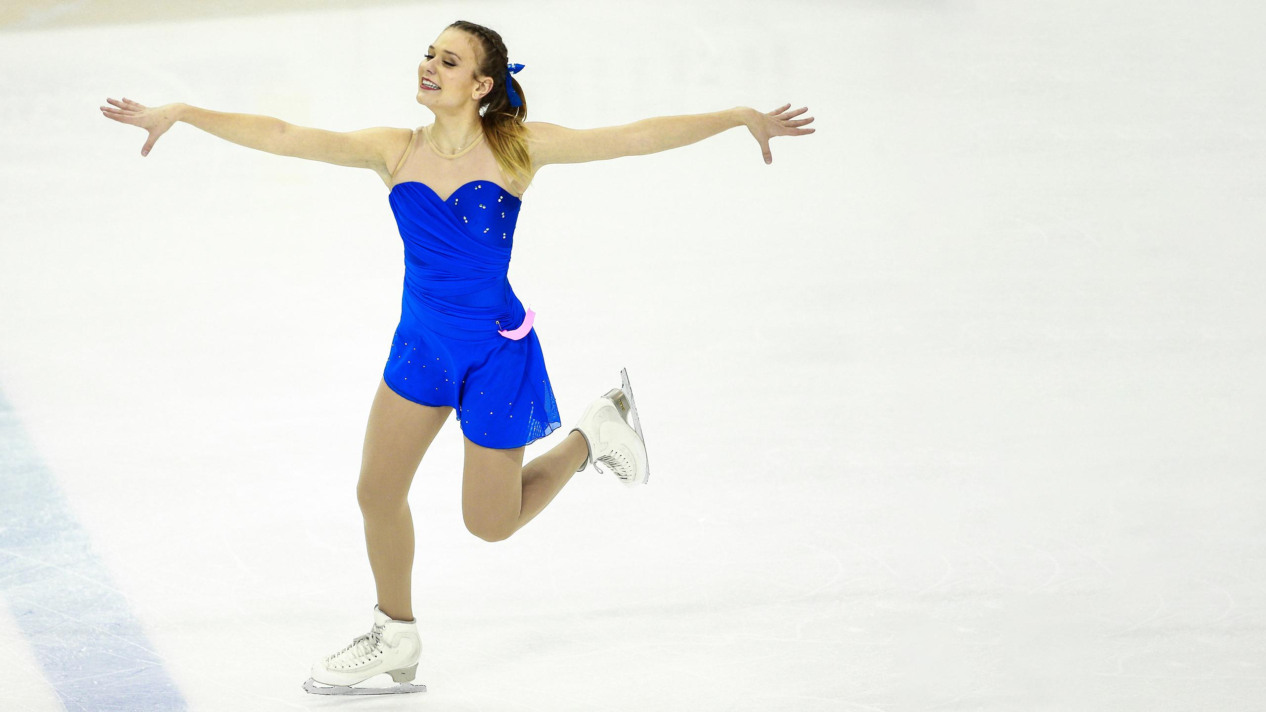 A figure skater smiling as she balances on one skate with her arms extended.