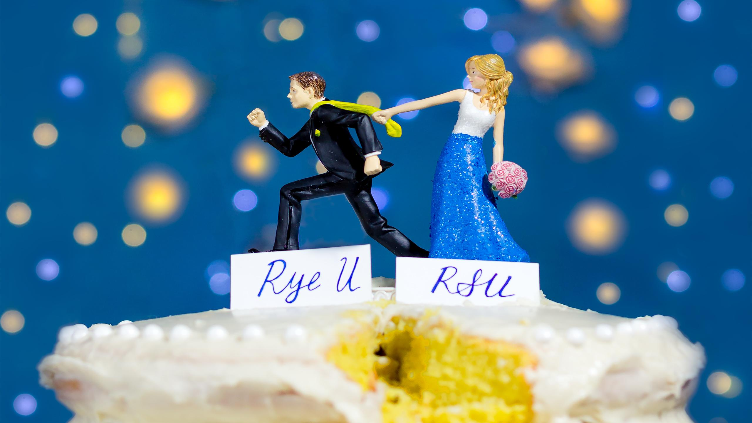 Wedding cake toppers showing a bride holding onto her groom's tie as he tries to run away. A nameplate under the bride says RSU and under the groom says Rye U.