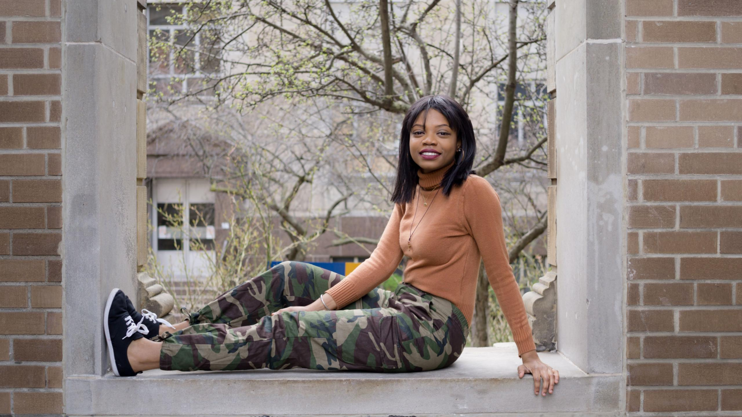 Yanique Brandford sitting on a window ledge with a brick wall around the window ledge.