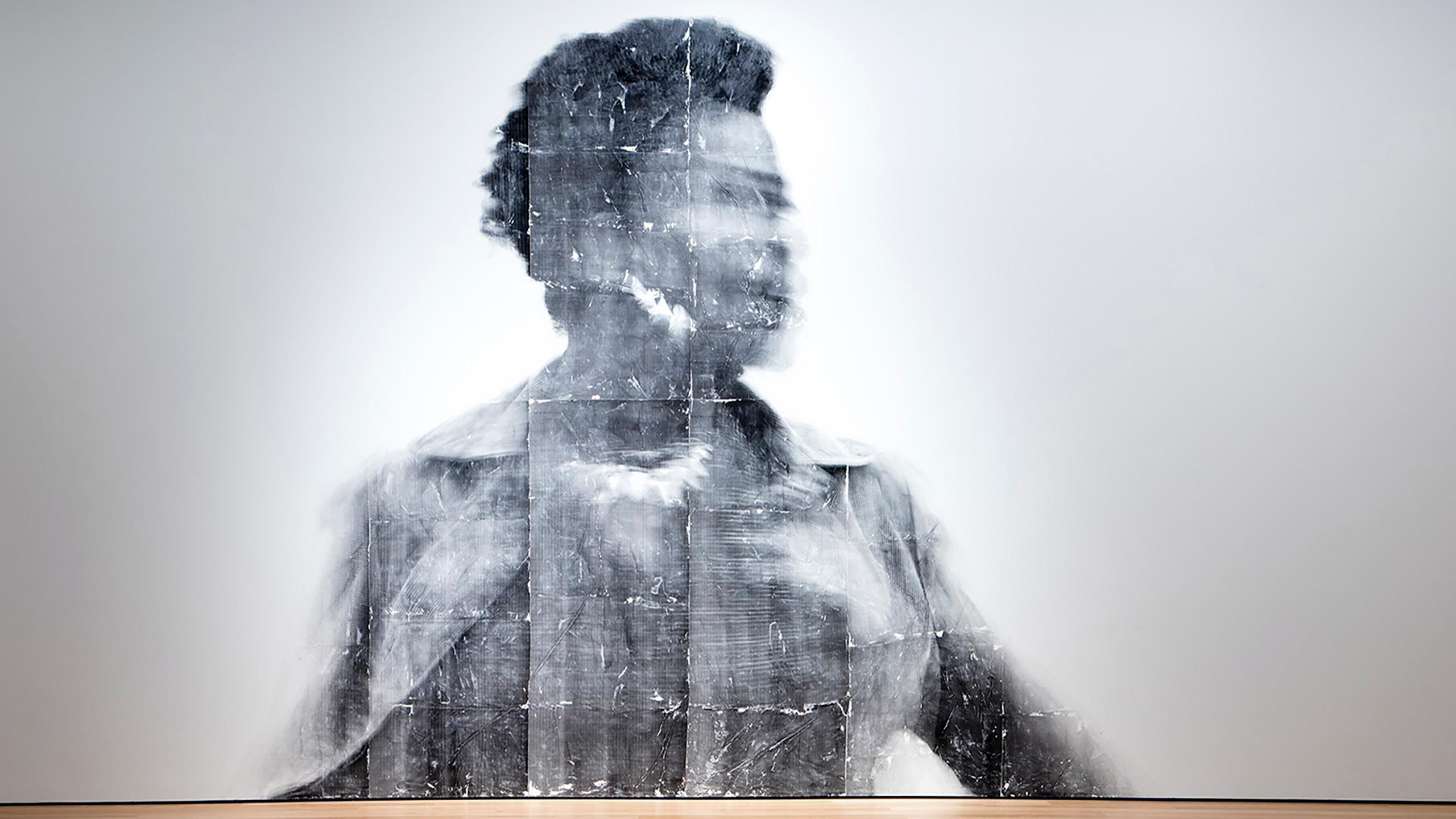 A photo of a Black woman projected on a wall