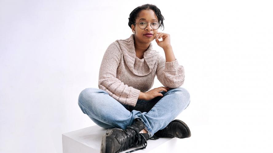 A young person posing cross-legged.
