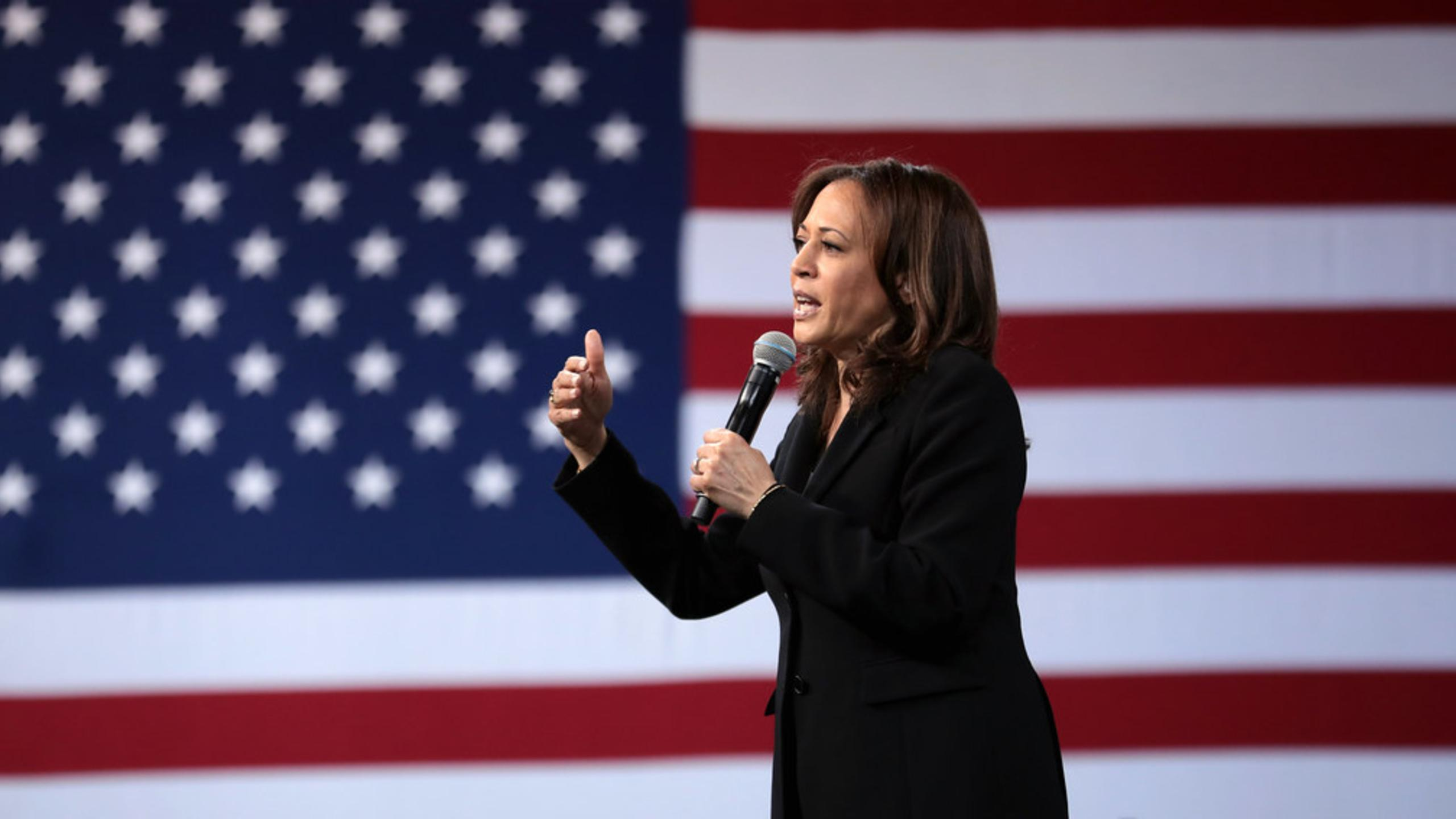Kamala Harris wearing a black suit holding a microphone in front of an American flag