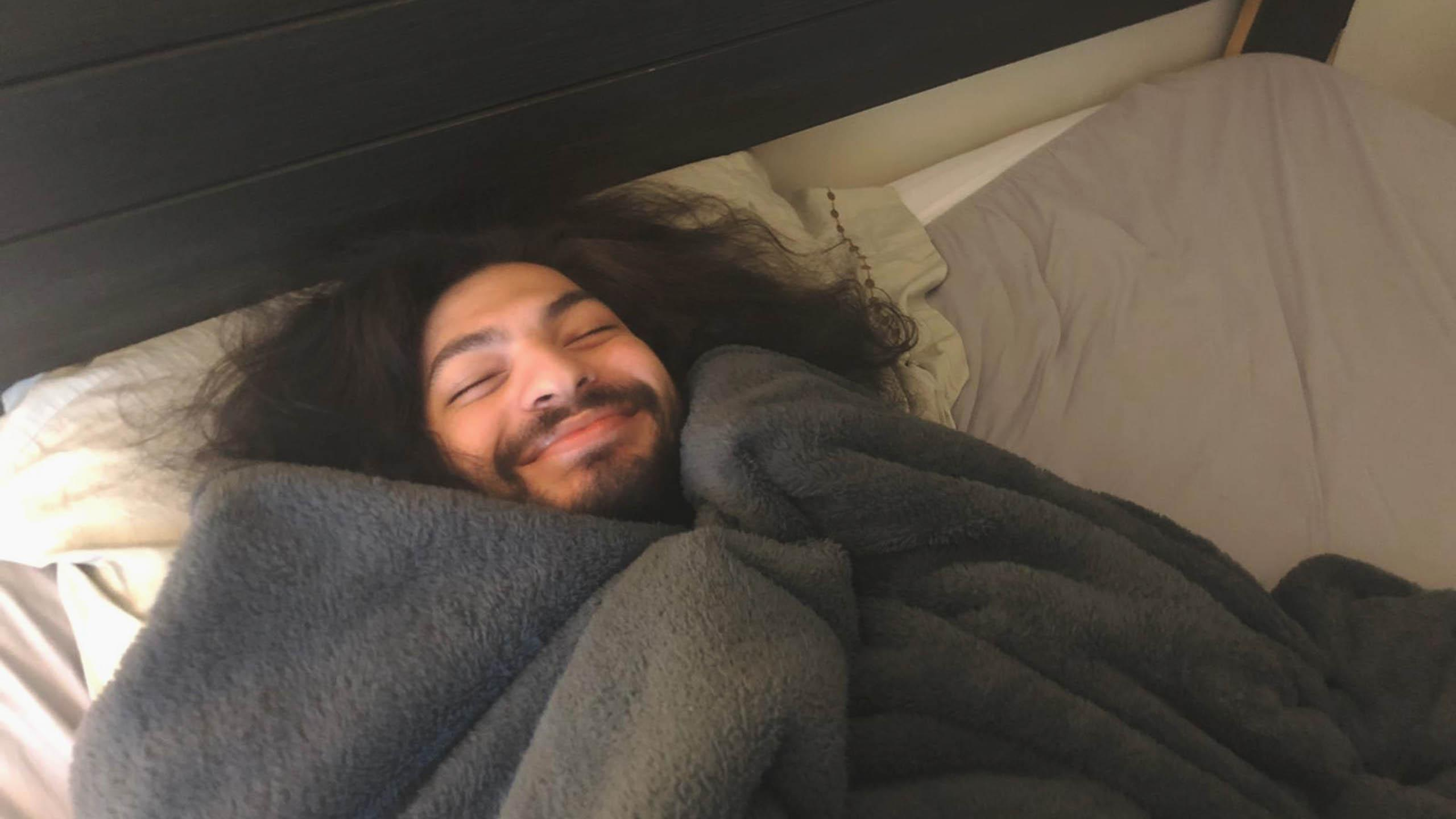 Man laying on bed, covered with blanket, smiling happily.