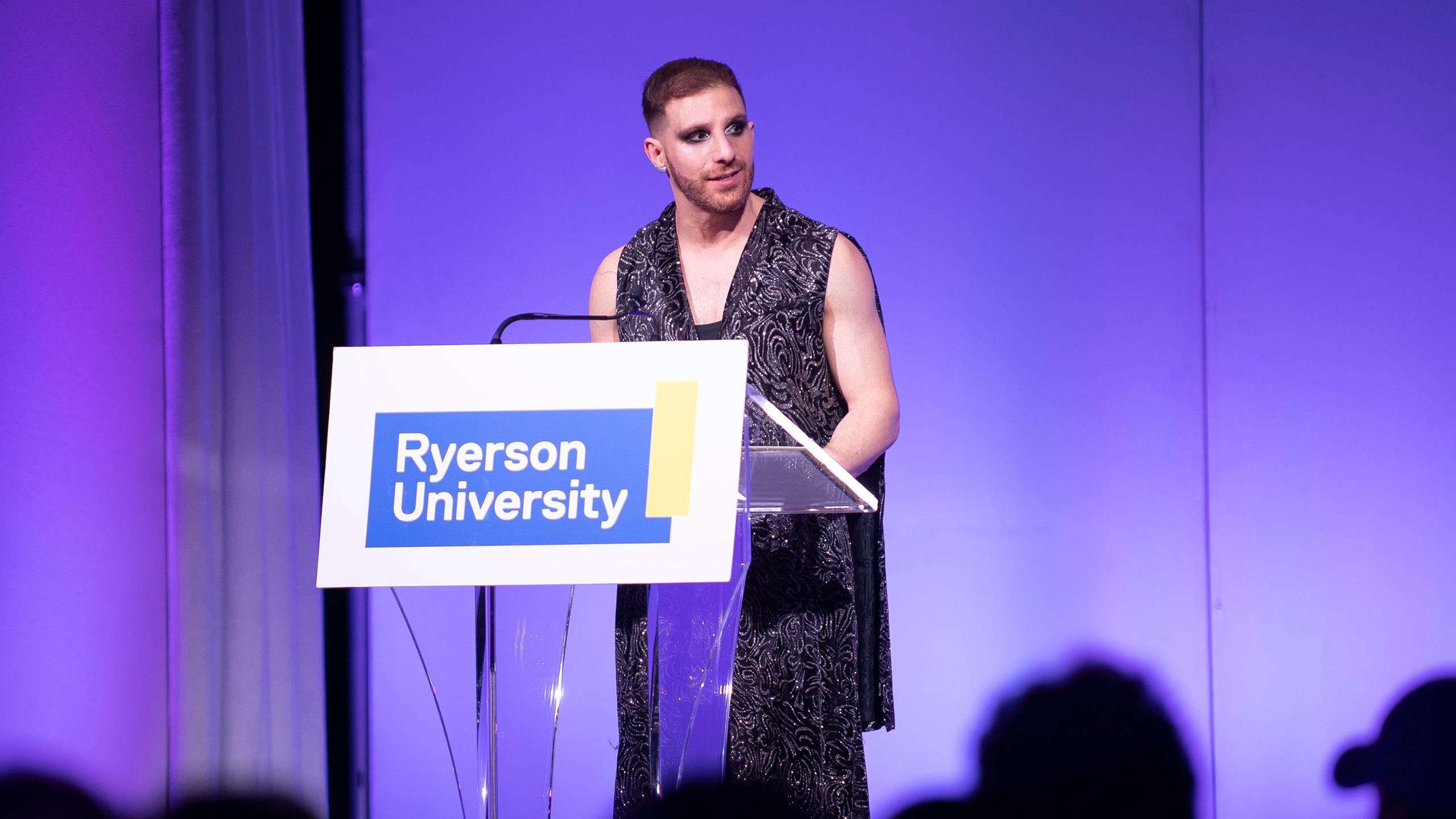 A photo of Ben Barry at a podium that says Ryerson University.